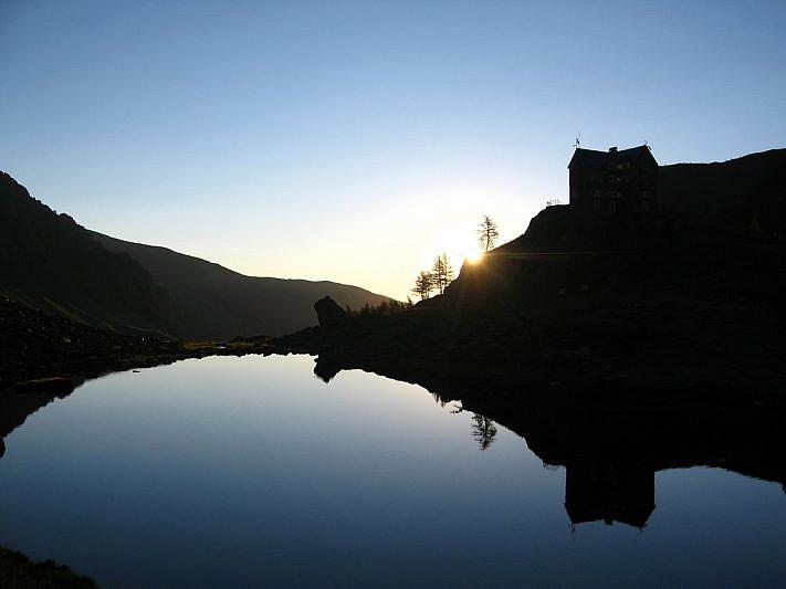 I primi raggi di sole dal lago verso il rifugio Migliorero (2094 m)
