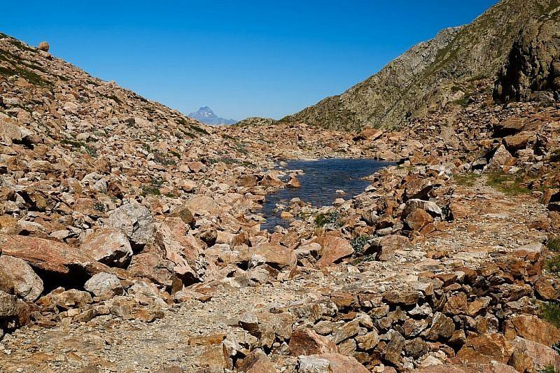 Tra le rocce rossastre con, al fondo, il Monviso