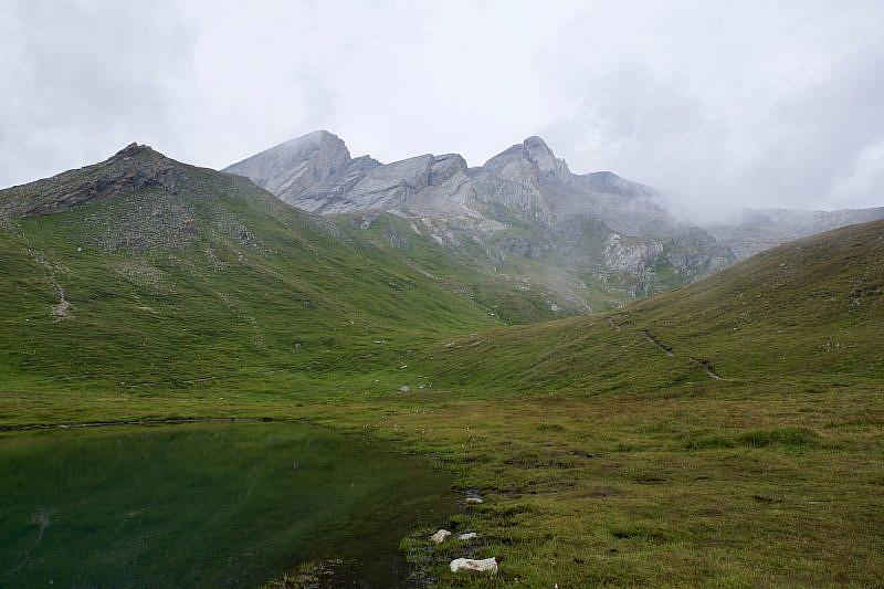 A destra del lago la traccia da imboccare. Sullo sfondo Pan di Zucchero (sinistra) e Pic d'Asti (destra).